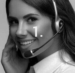 Frau mit Headset telefoniert und berät Kunden. Im Vordergrund steht 1.